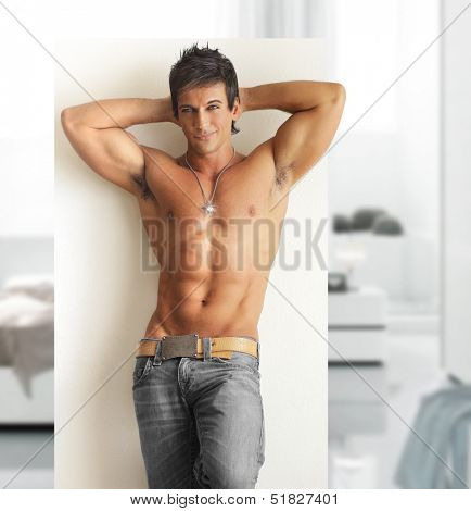 Sexy smiling shirtless male model with muscular body and abs in modern contemporary setting