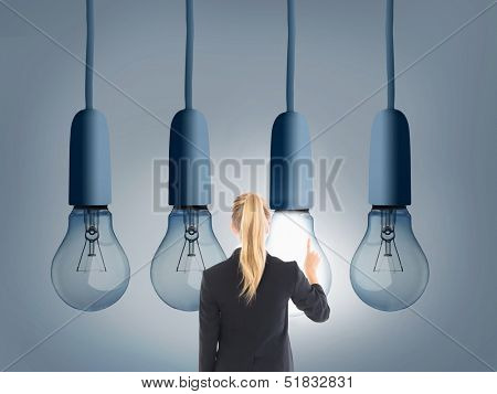 Composite image of blonde businesswoman pointing at huge light bulb on grey background poster