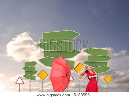 Composite image of attractive glamour woman holding a broken umbrella standing before road signs in the sky