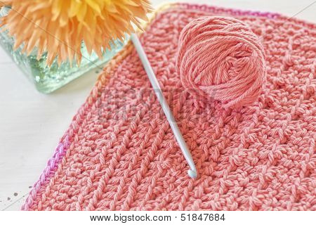 A crocheted dishcloth with crotchet hook and ball of yarn sitting alongside a vase of flowers.