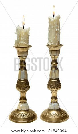 Two burning old candles in Golden candlesticks with mother of pearl. Isolated on white background.