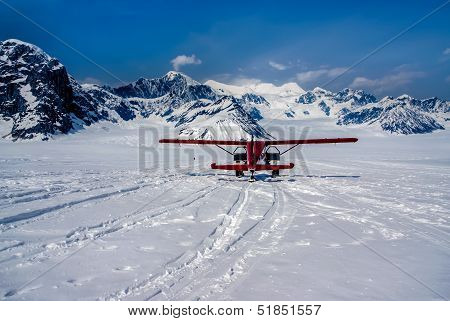 Snow Plane Landing on Ruth Glacier in Denali National Park, Alaska.  The Great Alaskan Wilderness.  A Beautiful Snowscape of Rock, Snow, and Ice. poster