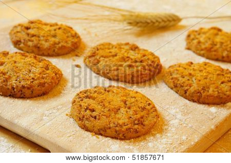 some bran flake cookies on a wooden worktop stained with floor and with some wheat ears