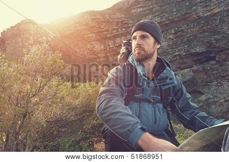 portrait of adventure man with map and extreme explorer gear on mountain with sunrise or sunset
