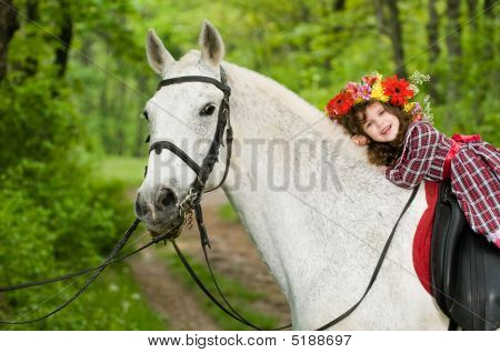 Smiling little girl in floral wreath riding horse in the forest poster