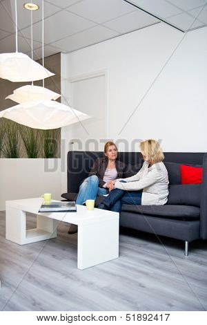 Two business women talking on a couch in a corporate waiting area before a sales pitch - creative industry