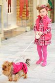 Little beautiful girl in dress leads small dog on leash in clothes in store. poster