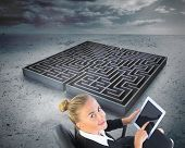 Composite image of blonde businesswoman sitting on swivel chair with tablet with a big maze in the background poster