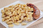 a plate with botifarra amb mongetes, fried white beans and sausage typical of Catalonia, Spain poster