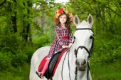 Little cute girl in floral wreath riding horse in the forest poster
