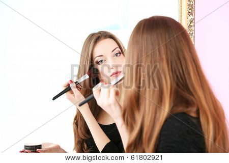 Young beautiful woman making make-up near mirror poster