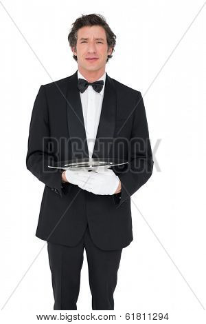 Portrait of confident waiter holding empty tray over white background