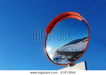 Road circular mirror with blue sky in the background