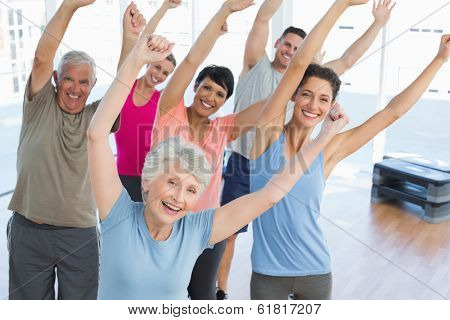 Portrait of smiling people doing power fitness exercise at yoga class in fitness studio poster