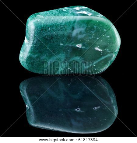 Jade  mineral stone close up with reflection on black surface background