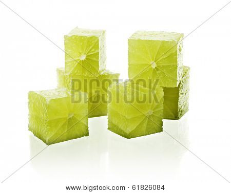 Real lime fruit cut into cubes on reflective white background.