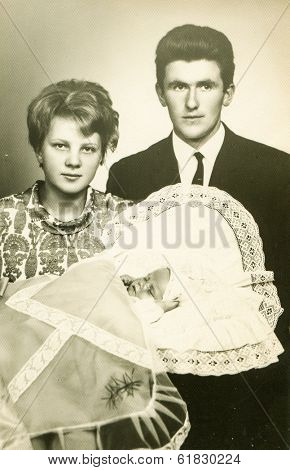 LODZ, POLAND, CIRCA 1970's - vintage photo of godparents with a baby in traditional baby's sleeping bag for christening