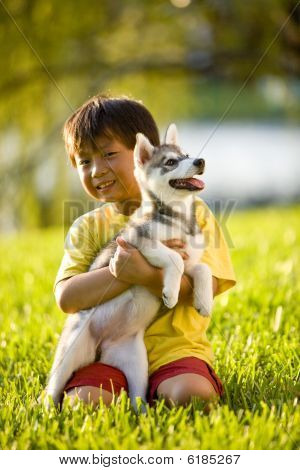 Young Asian boy hugging puppy sitting on grass