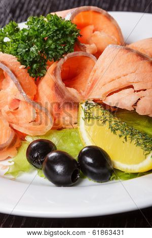 Slices Of Red Fish With Lemon And Olives On Plate
