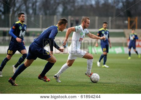 KAPOSVAR, HUNGARY - MARCH 16, 2014: Unidentified players in action at a Hungarian Championship soccer game - Kaposvar (white) vs Puskas Akademia (blue).