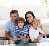 Portrait of happy family smiling at the camera in living-room poster
