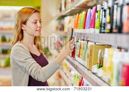 Young woman comparing prices with a smartphone app in a drugstore