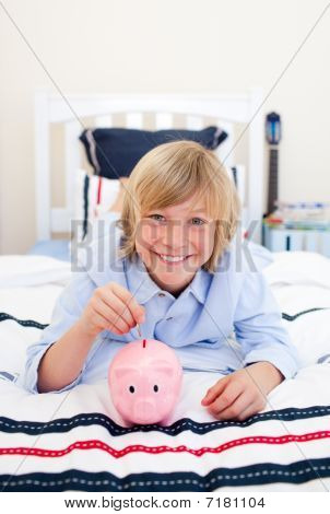 Smiling Boy Inserting A Coin In A Piggybank Lying Down On Bed