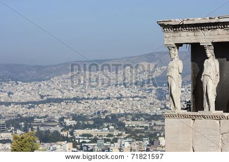 The caryatids in the Erechtheion of Erechtheum the ancient greek temple in the Acropolis of Athens with a view of the cityscape in Athens Greece. poster
