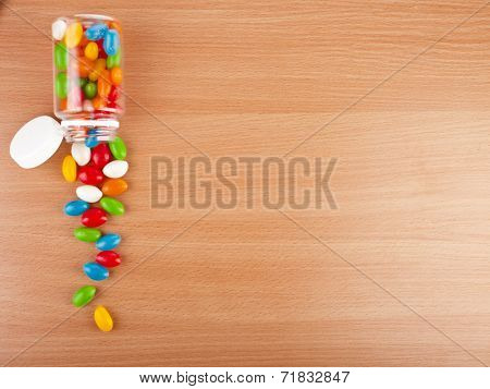 Colored Pills spilled from a bottle  on surface wooden table. top view