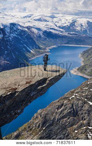 Hiker peering over the edge of Trolltunga rock Norway poster