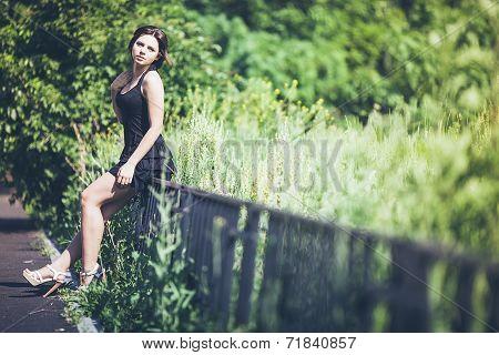 Girl in black dress on fence