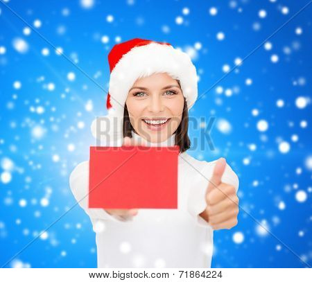 christmas, holdays, people, advertisement and sale concept - happy woman in santa helper hat with blank red card showing thumbs up gesture over blue snowy background