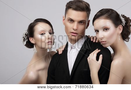 Love Triangle. Two Charming Women Hugging A Handsome Man