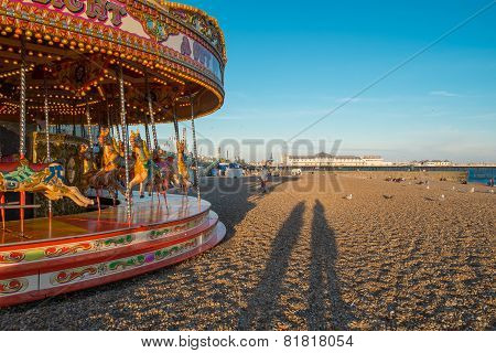 Shadows of people on Brighton beach next to a carousel