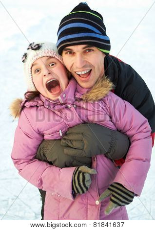 Dad hug his daughter and have fun in winter park