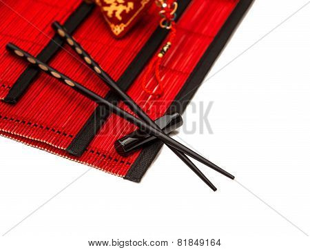 Black Chopsticks On Red Bamboo Mat. Chinese New Years Lucky Charm