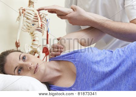 Male Osteopath Treating Female Patient With Shoulder Problem poster