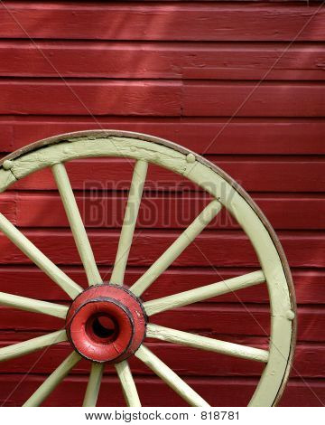 Old Chipped Wagon wheel with red wall in the Background poster