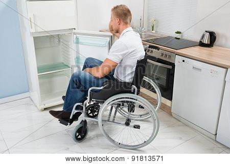 Disabled Man On Wheelchair Look Into An Empty Refrigerator poster