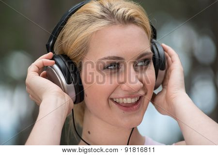 Young woman enjoying music on her portable MP3 player