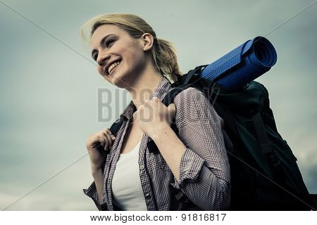 Portrait of a young female backpacker, low angle view