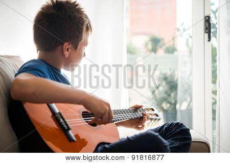 Cute boy playing guitar
