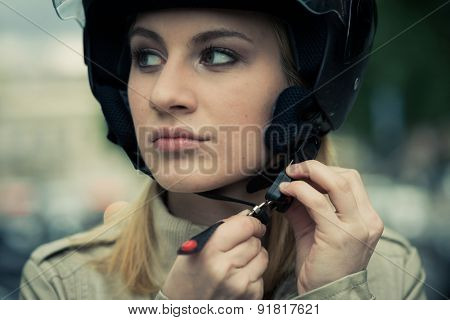 Young woman taking on/off her helmet