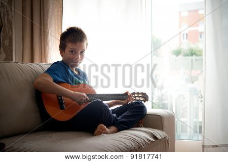 Portrait of a cute little boy posing with guitar