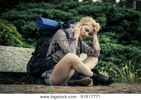 Exhausted and desperated young female backpacker