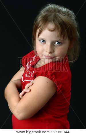 Small girl with arms crossed looking at camera on black
