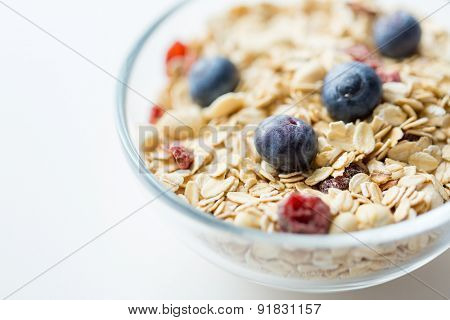 food, healthy eating and diet concept - close up of bowl with granola or muesli on table