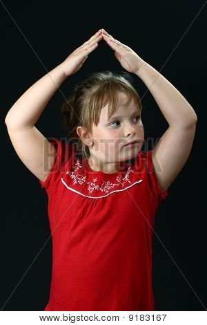 Small girl making roof from hands above her on black