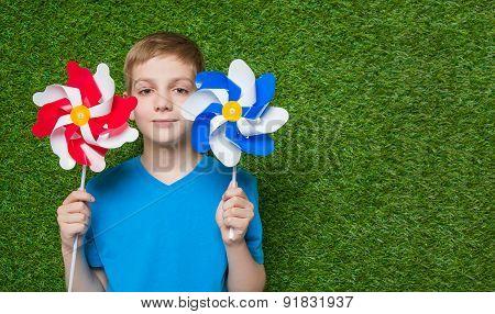Smiling boy holding pinwheels