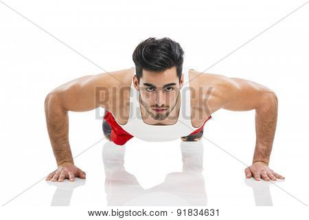 Athletic young man making push-up, isolated over a white background